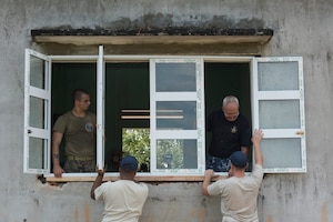 U.S. and Australian service members representing Pacific Angel (PAC ANGEL) 18-2 install a window at a classroom at Phan Dinh Phung Primary School in Tam Phuoc commune, Phu Ninh district, Vietnam, Sept. 11, 2018.