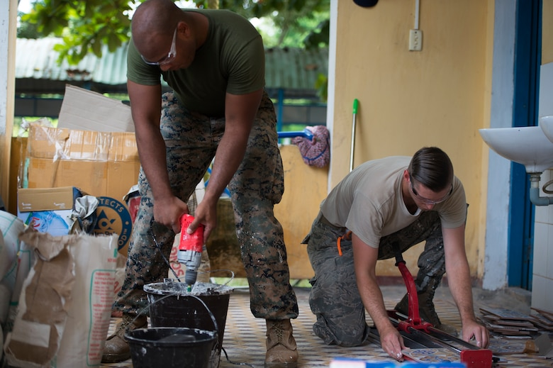 (Left) U.S. Marine Corps Sgt. David Tyson, 7th Engineer Support Battalion combat engineer, mixes grout as U.S. Air Force Staff Sgt. Zach Julian, 145th Airlift Wing water and fuel system maintenance craftsman, cuts tile during Pacific Angel (PAC ANGEL) 18-2 at Nguyen Hien Junior High School in in Phu Thinh town, Phu Ninh district, Vietnam, Sept. 11, 2018.