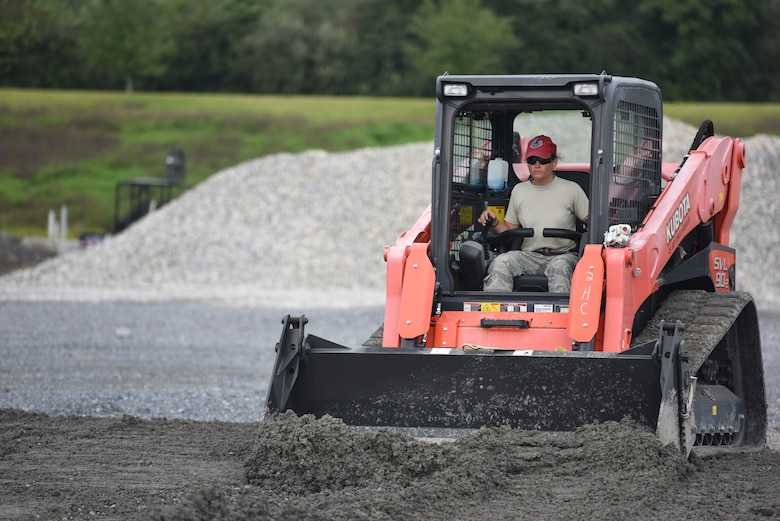 Senior Airman Helene Jones, a heavy equipment operator with the 201st RED HORSE Squadron, Fort Indiantown Gap, Pennsylvania, participates in a field training exercise Sept. 7, 2018. Jones was in charge of evenly distributing 1 1/2 feet of stone that was being laid as the foundation for a K-span building. (U.S. Air National Guard photo by Senior Airman Julia Sorber/Released)