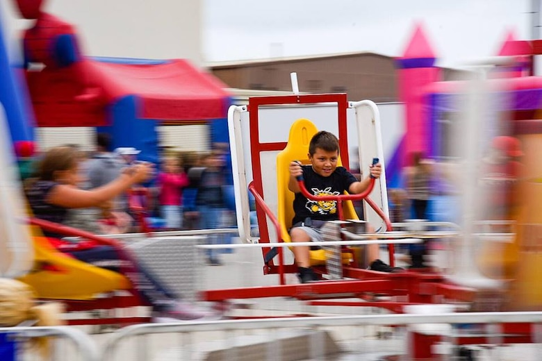 "A child plays on a carnival ride at the Frontiers in Flight Open House and Air Show Sept. 8, 2018, at McConnell Air Force Base, Kansas. The show offered a ""Kid Zone"" where children could play while waiting for their favorite aerobatic performances. (U.S. Air Force photo by Airman 1st Class Michaela R. Slanchik)"