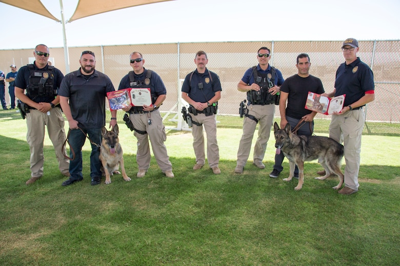 Jacob Lucero(second for left) and Nadeem Seirafi ((second from right) hold the leashes of Colli and Ricsi during the two Military Workings Dogs' retirement ceremony at the K-9 Training Field adjacent to the Adam Leigh Cann Canine Facility aboard Marine Corps Logistics Base Barstow, Calif., Sept. 12. The two handlers partnered with their K-9 companions on the beat and are now adopting the two dogs as they retire from active duty. Lieutenant Steven Goss, (far right) kennel master, Marine Corps Police Department, presented the two dogs with retirement certificates. The other officers in the photo also partnered with Colli and Ricsi at different times in their careers.