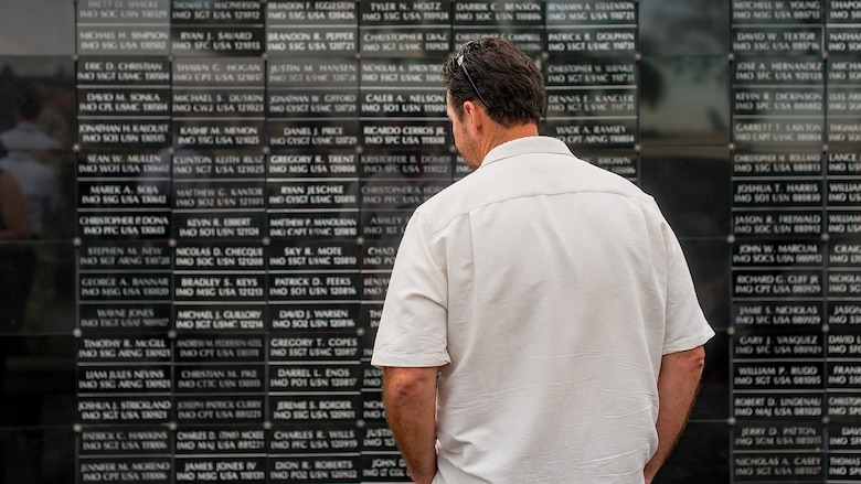 A Team MacDill Member pays respects to the names on the U.S. Special Operations Command Memorial after a 9/11 memorial ceremony held at MacDill Air Force Base, Fla., Sept. 11, 2018. The remembrance ceremony was held in honor of those who died during the attacks.