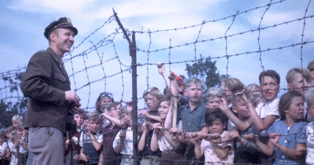 "Lt. Gail Halvorsen, ""The Candy Bomber,"" greets children of isolated West Berlin sometime during 1948-49 after dropping candy bars from the air on tiny parachutes. (U.S. Air Force photo)"