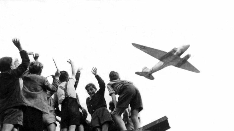 "German children in West Berlin wave to an Air Force transport aircraft as it comes in to land at Templehof Airport during ""Operation Vittles,"" better known as the Berlin Airlift in 1948. The USAF and United Kingdom Royal Air Force aircraft flew around the clock throughout the year and into 1949 when the Soviets reopened land routes on May 12. (U.S. Air Force photo)"