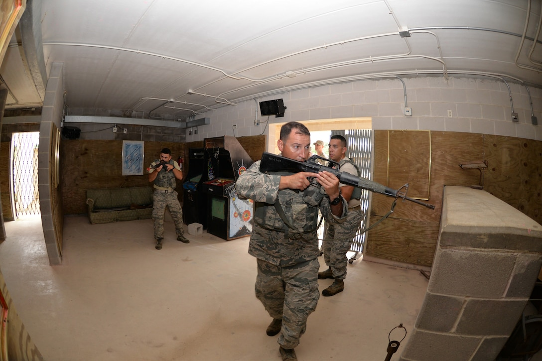 Air Force Reserve Command Defender Challenge Team Members Senior Airman Rick Cardona (left), and Tech Sgts. Francisco Gonzalez, and Hector Zamora, team leader, perform room-clearing exercises at Camp Bullis Military Training Reservation, Texas, Sept. 7, 2018.