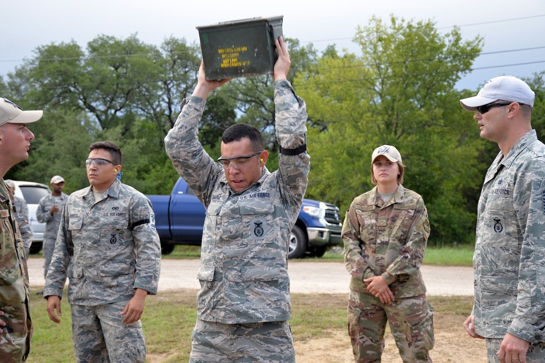 Tech Sgt. Hector Zamora, Air Force Reserve Command Defender Challenge team leader, performs 25 repetitions of lifting the ammo can as the first portion of his relay in the combat endurance event Sept. 13, 2018 at Camp Bullis Military Training Reservation, Texas.