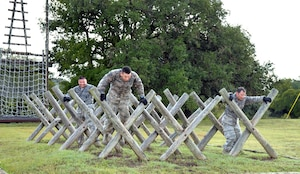 "Air Force Reserve Command Defender Challenge Team Members Tech. Sgt. Mariano Flores, Senior Airman Rick Cardona, and Tech Sgt. Francisco Gonzalez, navigate the ""Tough Nut"" obstacle at the Camp Bullis Military Training Reservation, Texas, Sept. 6, 2018."
