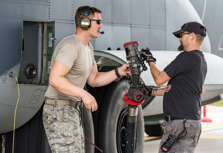 Alaska Air National Guard Tech. Sgt. David Hancock, assigned to the 176th Aircraft Maintenance Squadron, Joint Base Elmendorf-Richardson, Alaska,   passes the refueling hose to Brian Mace, 436th Aircraft Maintenance Squadron aircraft worker, after refueling a HC-130J Sept. 13, 2018, at Dover Air Force Base, Del. Members and equipment from the 176th Wing, 176th Aircraft Maintenance Squadron, 211th and 212th Rescue Squadrons at JBER arrived at Dover on Sept. 12 to support hurricane relief efforts when called upon. (U.S. Air Force photo by Roland Balik)