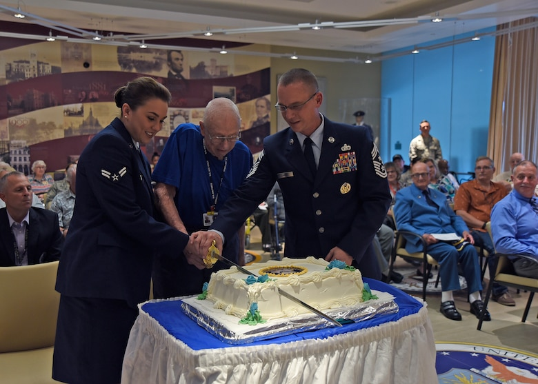 Chief Master Sgt. Thomas C. Daniels, 11th Wing and JBA command chief, retired Tech. Sgt. George Setzer, Armed Forces Retirement Home resident, and Airman 1st Class Skylar Armstrong, 1st Airlift Squadron flight attendant, cut a cake at the AFRH, D.C., Sept. 14, 2018. Joint Base Andrews Airmen joined retirees from the AFRH to celebrate the Air Force's 71st birthday. (U.S. Air Force photo by Senior Airman Abby L. Richardson)