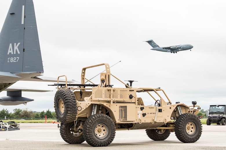 A Guardian Angel Air-droppable Rescue Vehicle assigned to the Alaska Air National Guard, 176th Wing, Joint Base Elmendorf-Richardson, Alaska, sits near the tail of a HC-130J while a C-17 Globemaster III flies in the background Sept. 13, 2018, at Dover Air Force Base, Del. Members and equipment from the 176th Wing, 176th Aircraft Maintenance Squadron, 211th and 212th Rescue Squadrons at JBER arrived at Dover on Sept. 12 to support hurricane relief efforts when called upon. (U.S. Air Force photo by Roland Balik)