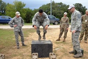 Senior Airman Lorenzo Fonseca, Air Force Reserve Command Defender Challenge team member, performs 25 repetitions of jumping from the ground to the box during the combat endurance relay Sept. 13, 2018 at Camp Bullis Military Training Reservation, Texas.
