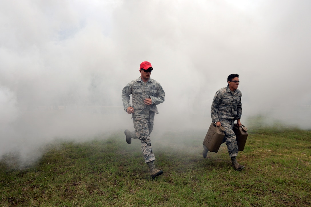 Senior Airman Lorenzo Fonseca, Air Force Reserve Command Defender Challenge team member, carries Jerry cans filled with water 50 meters from the starting point to the next station where he will attempt to shoot a target with an M4 carbine rifle during the combat endurance relay Sept. 13, 2018 at Camp Bullis Military Training Reservation, Texas.