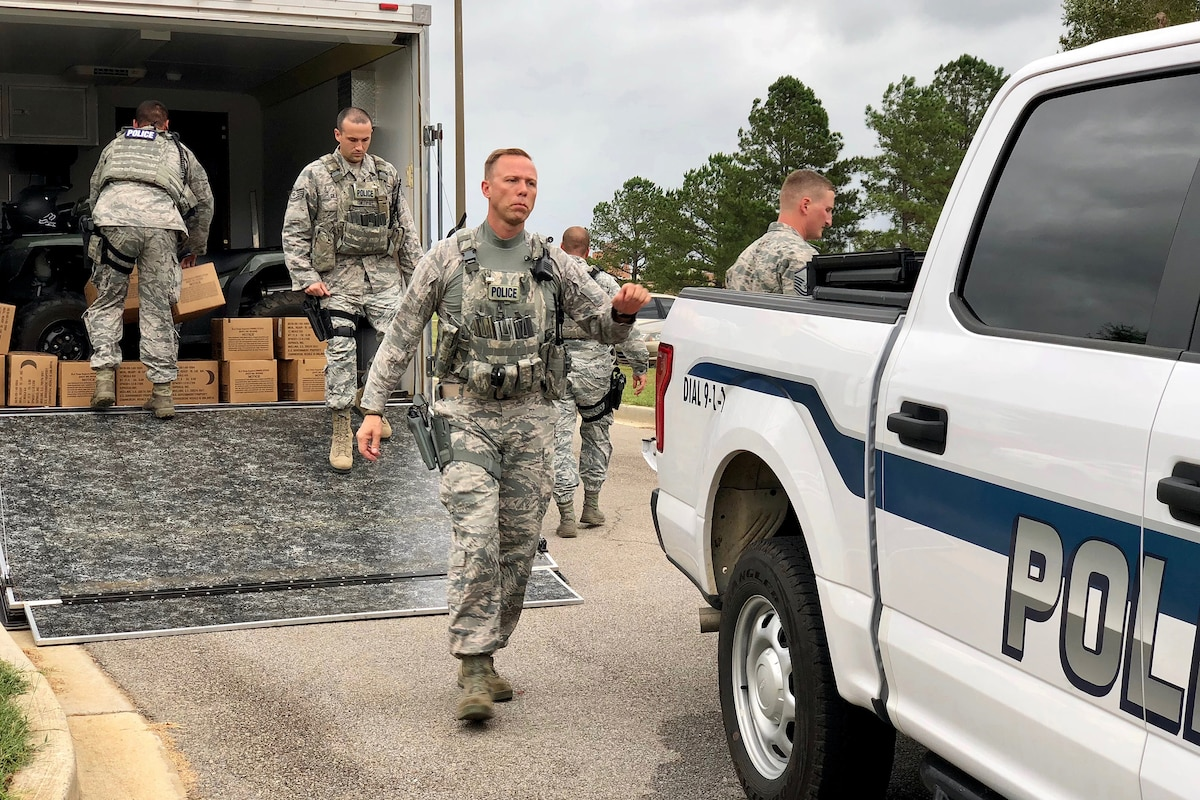 Airmen run to a police vehicle as they deploy to help search and rescue efforts following Hurricane Florence.