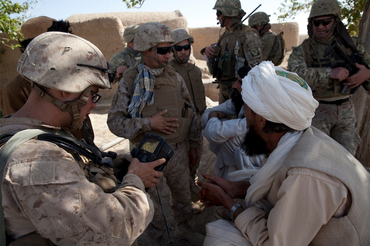 U.S. Marine Corps Staff Sgt. Paul Rogers, a team leader with Georgian Liaison Team 9, uses a Secure Electronic Enrollment Kit (SEEK II) on patrol in Mohammad Abad, Helmand province, Afghanistan, July 23, 2013.