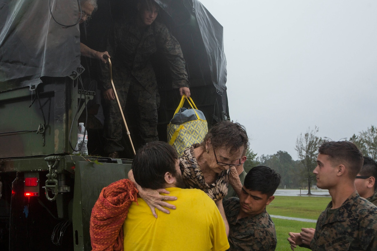 Marines help a resident get off the back of a military vehicle.