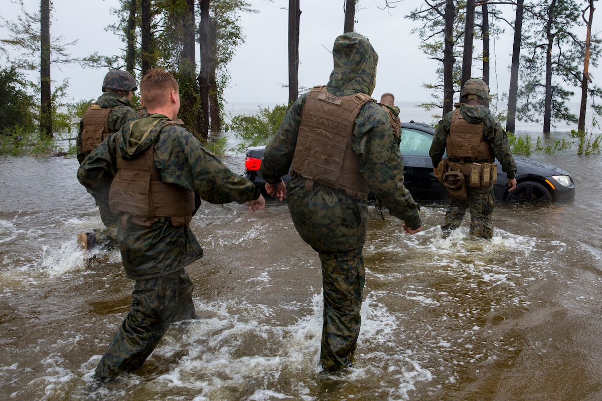 Marines run to help push a car out of floodwaters on Marine Corps Base Camp Lejeune.