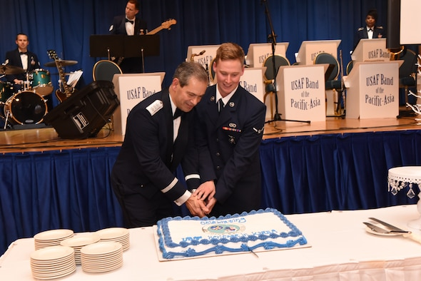U.S. Air Force Lt. Gen. Kenneth S. Wilsbach, Seventh Air Force commander, and U.S. Air Force Airman Marcus Davidson, assigned to the 51st Civil Engineer Squadron fire and emergency services flight, use a ceremonial sword to cut the cake during an Air Force 71st Birthday Ball at Osan Air Base, Republic of Korea, September 15, 2018.
