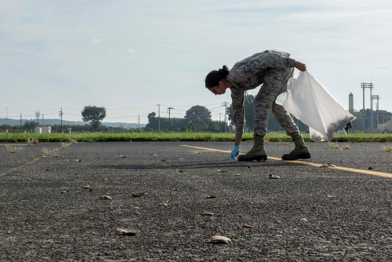 An Airman from the 374th Airlift Wing picks up a piece of debris remaining from 2018 Japanese-American Friendship Festival fireworks show during a foreign object debris walk at Yokota Air Base, Japan, Sept. 17, 2018.