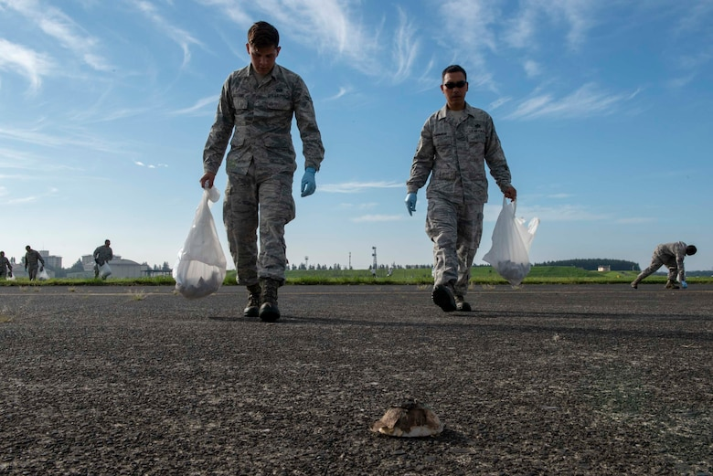 Airmen from the 374th Airlift Wing search the flightline for debris during a foreign object debris walk following the 2018 Japanese-American Friendship Festival at Yokota Air Base, Japan, Sept. 17, 2018.