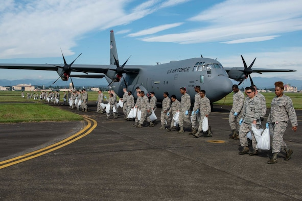 The Airmen from the 374th Airlift Wing perform a foreign object debris walk following the 2018 Japanese-American Friendship Festival at Yokota Air Base, Japan, Sept. 17, 2018.