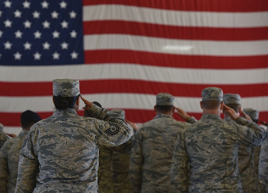 U.S. Air Force Airmen stand and salute the flag during the singing of the national anthem at a 9/11 remembrance ceremony in Hangar 5 at Tyndall Air Force Base, Fla., Sept. 11, 2018. The ceremony started at the exact moment the first tower was hit to honor the people who died Sept. 11, 2001. (U.S. Air Force photo by Airman 1st Class Miranda M.B. Simpson)