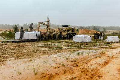Soldiers use heavy equipment to fill large sandbags.