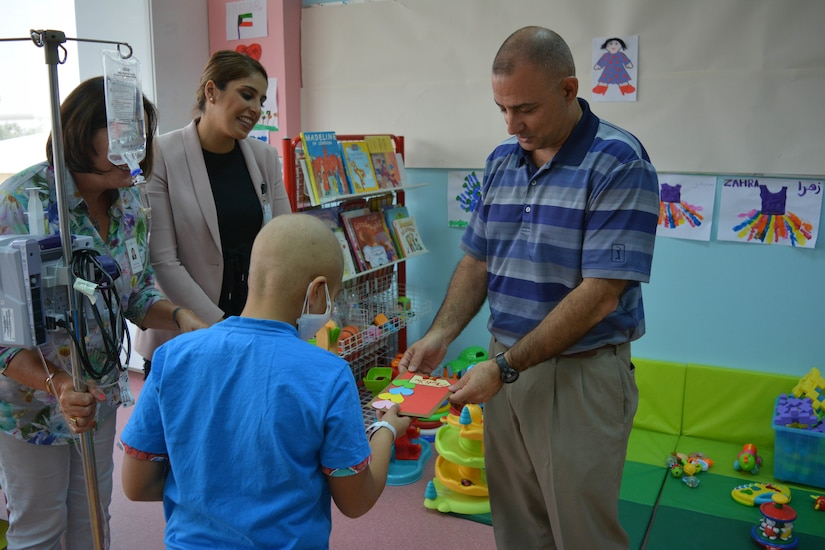 Brig. Gen. Mark McCormack, 28th Infantry Division/Task Force Spartan deputy commanding general – support, receives a thank you gift from one of the hospitalized children with whom he had just spent several hours playing games. More than 70 Soldiers are currently volunteering with Kuwait Association for the Care of Children in Hospitals, rotating small groups of Soldiers through weekly visits with children in two different hospitals.