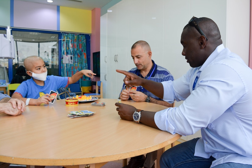 Sgt. 1st Class Mike Lewis, 28th Infantry Division/Task Force Spartan civil affairs NCO plays a highly contested game of Uno with his new friend on Sept. 4th.  For the past two months, TFS soldiers have been volunteering with the Kuwait Association for the Care of Children in Hospitals.