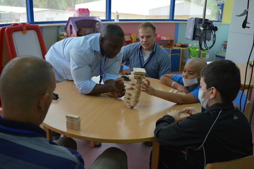 Sgt. 1st Class Mike Lewis, 28th Infantry Division/Task Force Spartan civil affairs NCO tumbles the Jenga tower during a play day visit with hospitalized children on Sept. 4th. For the past two months, TFS soldiers have been volunteering with the Kuwait Association for the Care of Children in Hospitals.