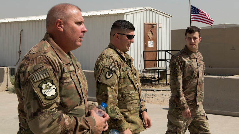 U.S. Army Capt. Joshua Paille, middle, commander of Headquarters and Headquarters Detachment 1109th Theater Aviation Sustainment Maintenance Group, attached to Task Force 22, leads his father, U.S. Air Force Chief Master Sgt. Andre Paille, a project manager with the 214th Engineering Installation Squadron, Louisiana Air National Guard, attached to U.S. Air Force Central, left, and his former college classmate, U.S. Army Capt. Joseph Booth, commander of the 220th Public Affairs Detachment, attached to U.S. Army Central, on a tour of the airfield where he works at Camp Arifjan, Kuwait, Sept. 1, 2018. One of the greatest assets available to the Army are Soldiers and their families who continue a rich tradition of military service.