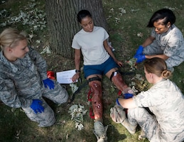 Emergency medical technicians, from the U.S. Air National Guard, place a tourniquet onto a role-player's simulate injuries in St. Paul, Minn., Aug. 16, 2018.
