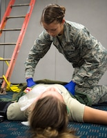 U.S. Air Force Airman 1st Class Victoria Mook, an emergency medical technicians from 192nd Medical Group, DET 1, checks a role-player for injuries in St. Paul, Minn., Aug. 17, 2018.