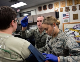 U.S. Air Force Airman 1st Class Angela Gallagher, right, and Staff Sgt. Patrick Doheney, emergency medical technicians, check the vitals of a role-player in St. Paul, Minn., Aug. 17, 2018.
