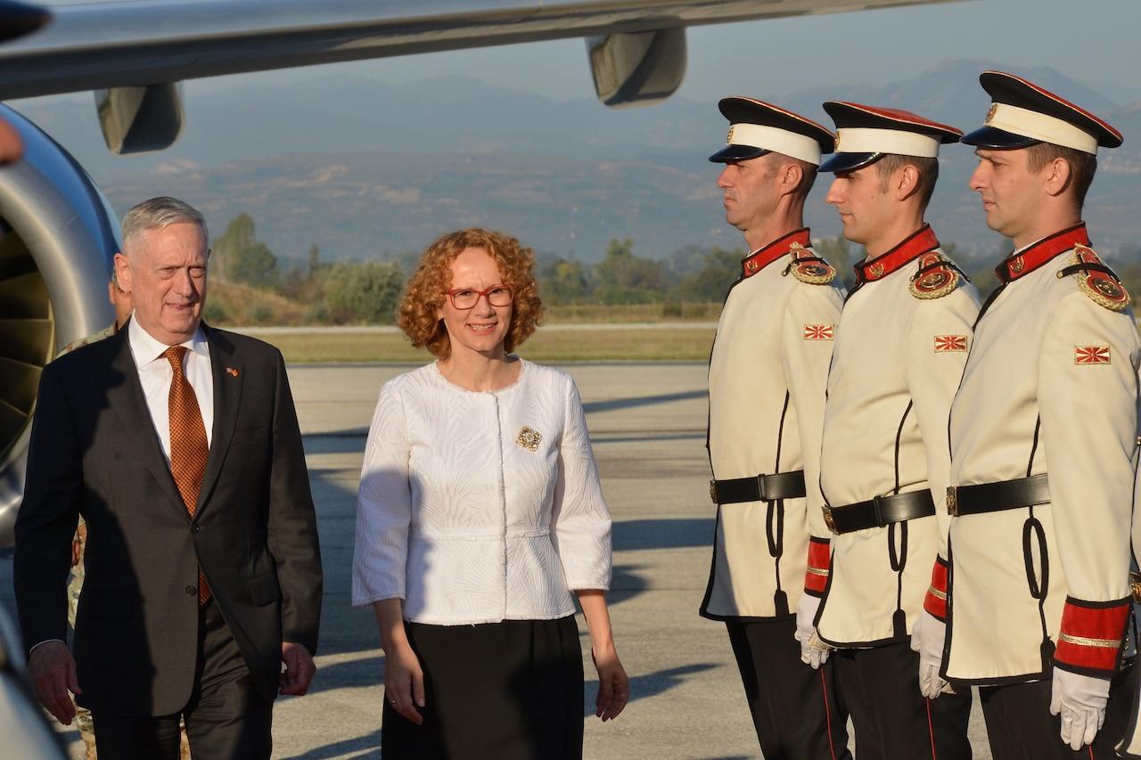 Defense Secretary James N. Mattis and Macedonian Defense Minister Radmila Shekerinska pass by military members in Skopje, Macedonia.