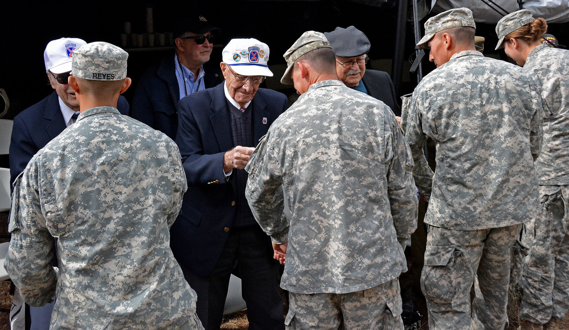 """Several 10th Mountain Division World War II veterans """"patched""""  Soldiers of 1st Battalion, 157th Infantry (Mountain), Colorado Army National Guard, during the historic re-patching ceremony at Camp Hale, Colorado Oct. 30, 2016, as the 1-157 IN (MTN) became part of the 10th Mountain Division. The 1-157th assumes its role as one of only three mountain infantry battalions in the U.S. Army, reconnecting the historic 10th Mountain Division to Colorado. (Photo by Army National Guard Staff Sgt. Lalita Laksbergs)"""
