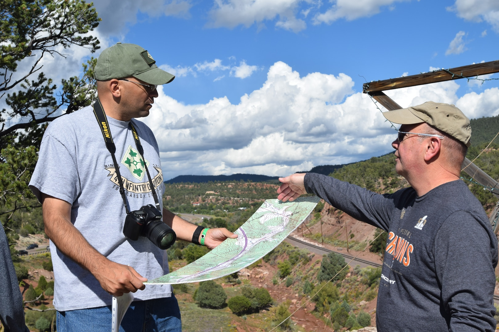 Senior Advisor to the Army National Guard U.S. Army Lt. Col. Shannon Espinoza, left, and Chief Warrant Officer 4 John Mudlo, right, a Colorado Army National Guard Soldier, discuss key aspects of the Apache Canyon terrain during the Colorado National Guard