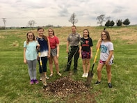 Young volunteers assisted by a park ranger, volunteered to plant a tree at Smithville Lake, Mo.