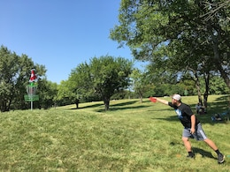 A disc golfer lets go toward the basket.