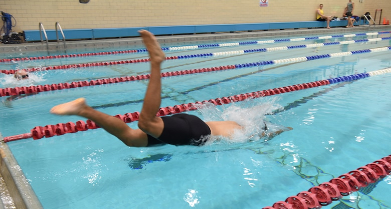 Staff Sgt. Roger Barrett, a 28th Maintenance Squadron aerospace ground equipment technician, dives into a pool at Ellsworth Air Force Base, S.D., Sept. 15, 2018. The 28th Force Support Squadron hosted the tri-to-b1 triathlon, which consisted of a 500-meter swim, a five-kilometer run and a 10-kilometer bicycle ride. (U.S. Air Force Photo by Airman 1st Class Thomas Karol)