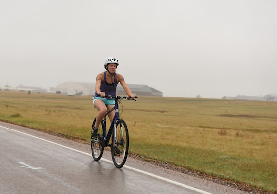 Corrie McFarland, a dependent, rides her bicycle during a triathlon at Ellsworth Air Force Base, S.D., Sept. 15, 2018. The 28th Force Support Squadron hosted the tri-to-b1 triathlon, which consisted of a 500-meter swim, a five-kilometer run and a 10-kilometer bicycle ride. (U.S. Air Force Photo by Airman 1st Class Thomas Karol)