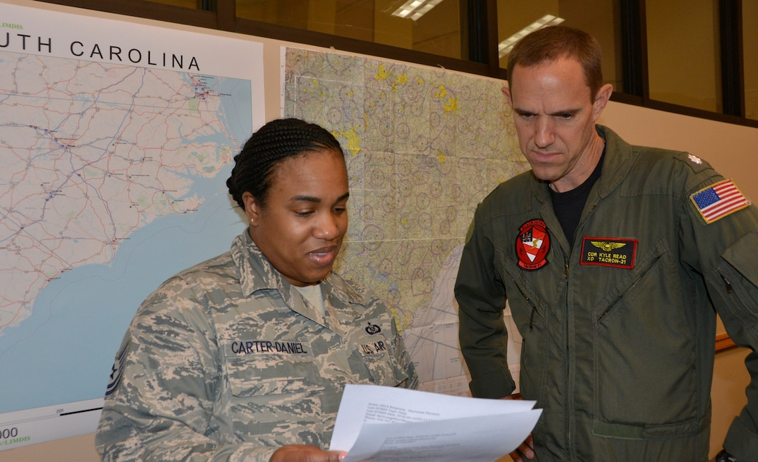 Tech.  Sgt. Theresa Carter-Daniels, Air Forces Northern Search and Rescue Operation Coordination Element controller, reviews information about potential search and rescue operations for Hurricane Florence with U.S. Navy CDR. Kyle Read, AFNORTH SAR OCE Naval Liaison Element. Total Force representation during AFNORTH's Defense Support of Civil Authorities efforts includes active-duty U.S. Navy, U.S. Marine Corps, U.S. Army, U.S. Coast Guard, and U.S. Air Force, Guard, Reservists and civilians. (Air Force photo by Mary McHale)