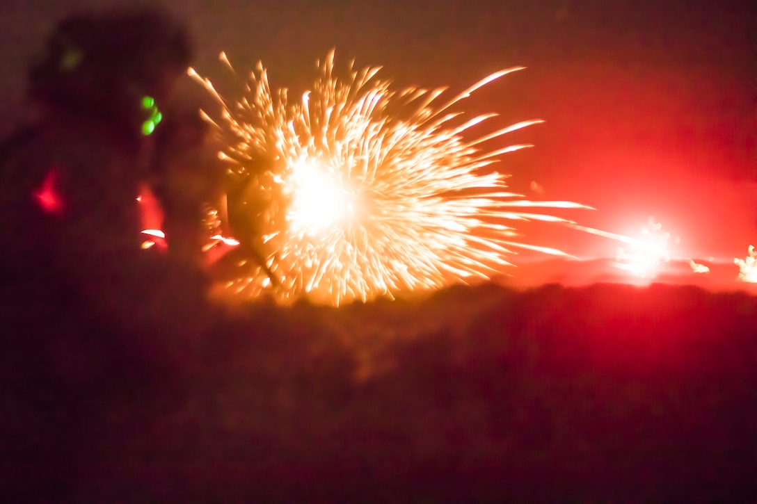 A Marine fires a machine gun at night, creating sparks and illuminating the area with red light.