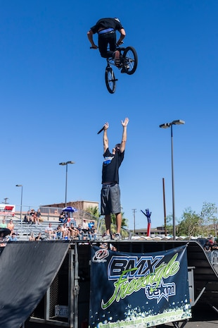 Jared Eberwein, professional BMX rider and X-Games athlete, hits a 540 bar spin over Dustin McCarty, Manager of McCarty BMX Freestyle Team and professional BMX rider, during the X-Games Action Sports Show at the Marine Corps Exchange parking lot aboard the Marine Corps Air Ground Combat Center, Twentynine Palms, Calif., Sept. 8, 2018. The X-Games provided a social recreational event in honor of the continuous service and sacrifice military personnel and family members make for the country. (U.S. Marine Corps photo by Pfc. Robin Lewis)