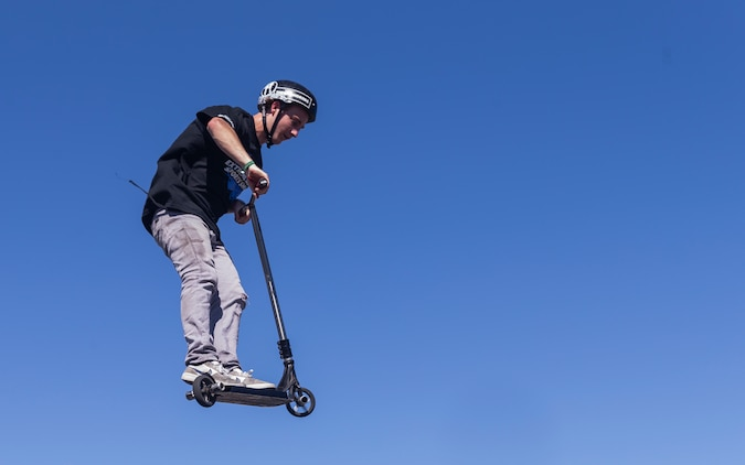 Bransyn Smith, professional Razor Scooter rider and X-Games athlete, performs a tail whip off of a box jump during the X-Games Action Sports Show at the Marine Corps Exchange parking lot aboard the Marine Corps Air Ground Combat Center, Twentynine Palms, Calif., Sept. 8, 2018. The X-Games provided a social recreational event in honor of the continuous service and sacrifice military personnel and family members make for the country. (U.S. Marine Corps photo by Pfc. Robin Lewis)