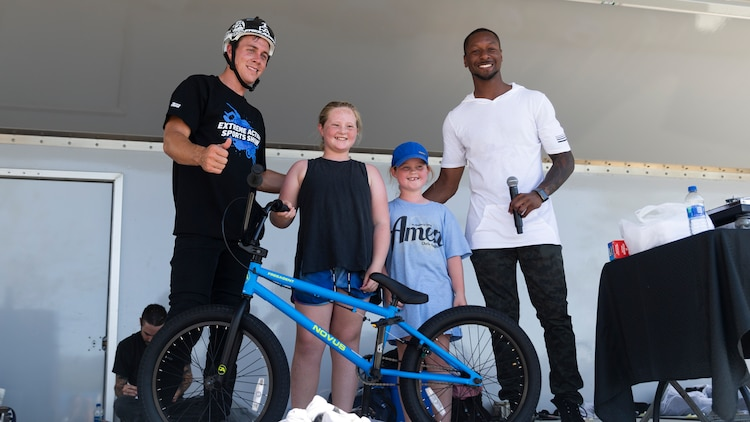 Parker and Dallas, sisters and Combat Center patrons, win a new, signed BMX bike during the X-Games Action Sports Show at the Marine Corps Exchange parking lot aboard the Marine Corps Air Ground Combat Center, Twentynine Palms, Calif., Sept. 8, 2018. The X-Games provided a social recreational event in honor of the continuous service and sacrifice military personnel and family members make for the country.  (U.S. Marine Corps photo by Pfc. Robin Lewis)