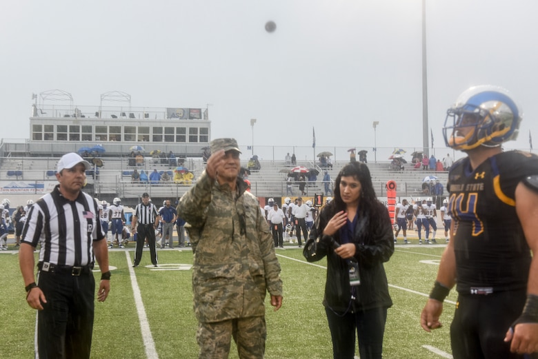 U.S. Air Force Col. Ricky Mills, 17th Training Wing commander, flips the coin to start the Angelo State University game against Texas A&M Kingsville during the Military Appreciation Day, at the LeGrand stadium, in San Angelo, Texas, Sept. 15, 2018. Texas A&M Kingsville won the toss, calling tails before the coin hit the ground. (U.S. Air Force photo by Aryn Lockhart/Released)