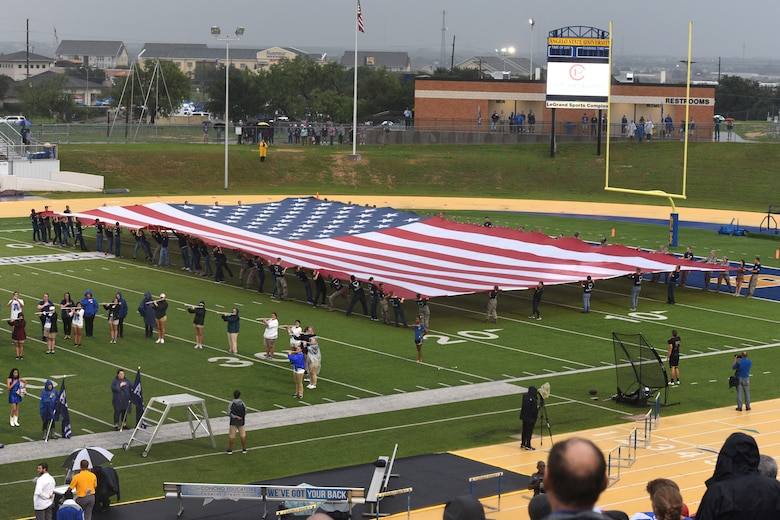 Angelo State University ROTC students unfold the American flag during the opening ceremonies of the Military Appreciation Day at LeGrand Stadium in San Angelo, Texas, Sept. 15, 2018. Along with the ceremonial unfolding of the flag, the ROTC students also celebrated each touchdown with a run to the end zone and pushups. (U.S. Air Force photo by Airman Zachary Chapman)