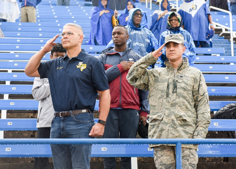 U.S. Air Force Col. Alejandro Ganster, 17th Training Wing chief of staff, Chief Master Sgt. Lavor Kirkpatrick, 17 TRW chief master sgt. and Col. Ricky Mills, 17 TRW Wing commander, pay respect while the national anthem plays during the Military Appreciation Day at the LeGrand stadium, in San Angelo, Texas, Sept. 15, 2018. Fans braved the rainy conditions to see the Angelo State University defeat Texas A&M Kingsville in their 30-14 victory. (U.S. Air Force photo by Aryn Lockhart/Released)
