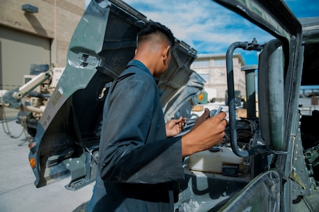 A Marine with the maintenance section, Headquarters and Service Company, 1st Tank Battalion, checks the oil level of a Humvee at the 1st Tank Battalion ramp aboard the Marine Corps Air Ground Combat Center, Twentynine Palms Calif., August 29, 2018.  Motor Transport Marines with 1st Tank Battalion increased overall readiness by 20% in the past three weeks by working extended hours. (Photo by Lance Cpl. Carley Vedro)