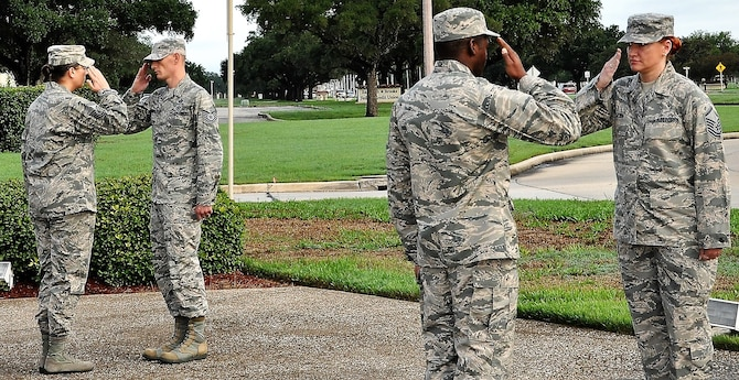 Master Sgt. Melissa Erwin, 340th Flying Training Group (far right) salutes the outgoing Airman as she prepares for her 30-minute stint during the POW\MIA Recognition Week Missing Man Vigil held Sept. 17 at Joint Base San Antonio-Randolph, Texas. (U.S. Air Force photo by Janis El Shabazz)